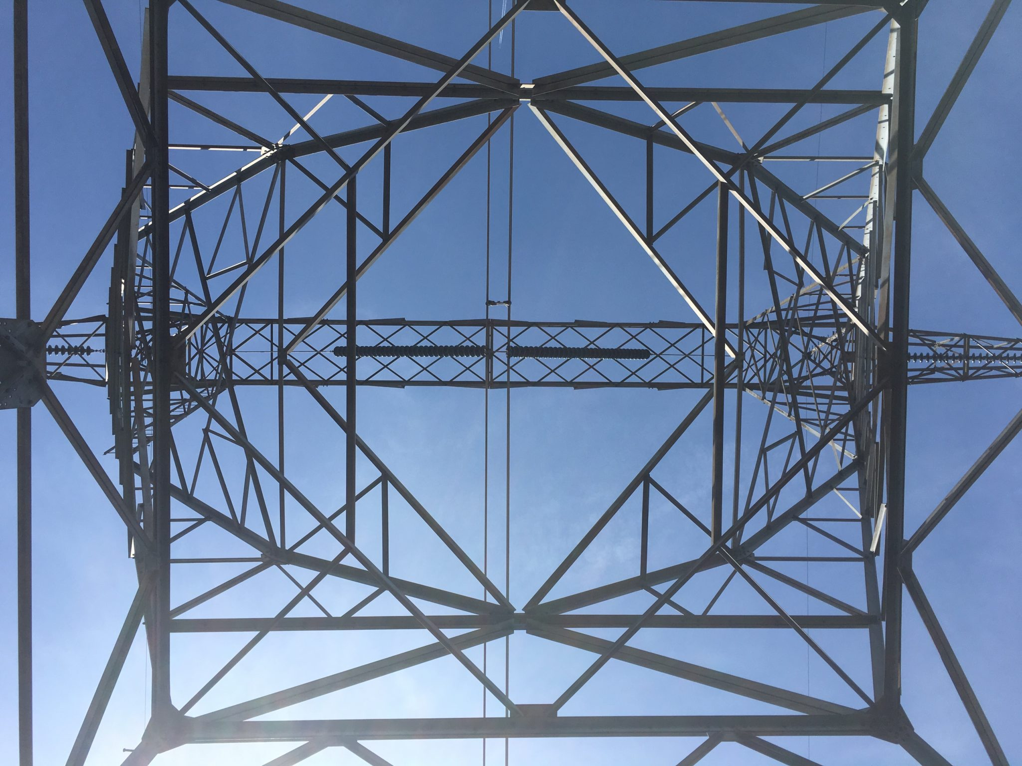 Looking up at a power line tower