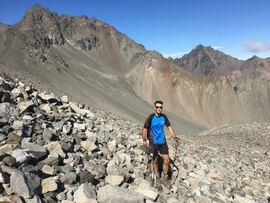Mt. Alarm and Mt. Mitre in the background as Kane hikes up the rock scree